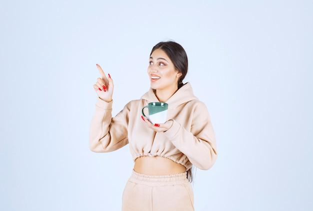 Giovane donna con una tazza verde che punta da qualche parte a sinistra