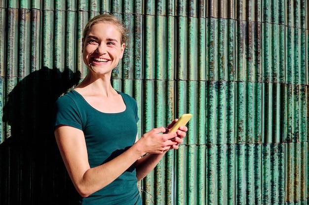 복사 공간이 있는 노란색 스마트폰을 사용하여 녹색 티셔츠를 입은 젊은 여성