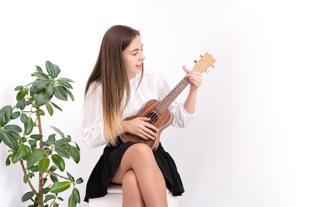 Молодая женщина с гитарой на белом фоне с копией пространства