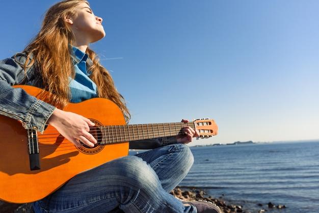 海の海岸に屋外のギターを持つ若い女性