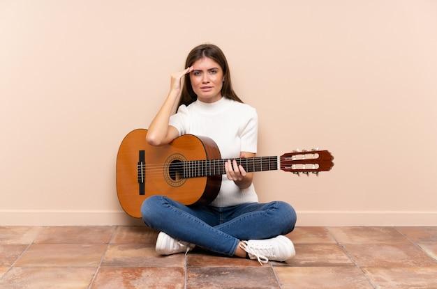 Молодая женщина с гитарой, сидя на полу недовольны и разочарованы чем-то. негативное выражение лица