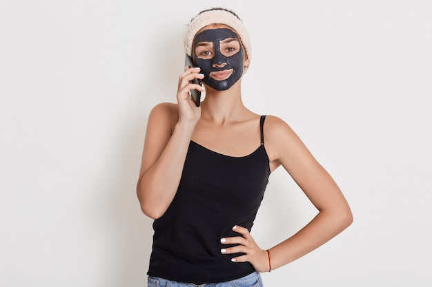 Young woman with hair band on head and black facial clay mask, talking via phone. spa beauty treatments, skin care at home, happy woman against white wall.