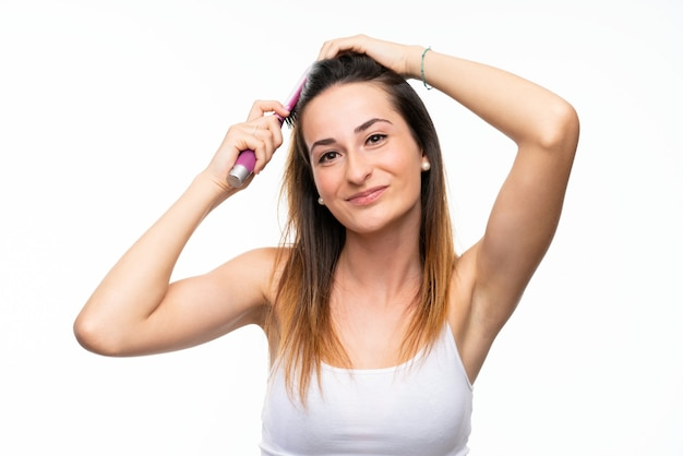 Young woman with hair comb over isolated white wall