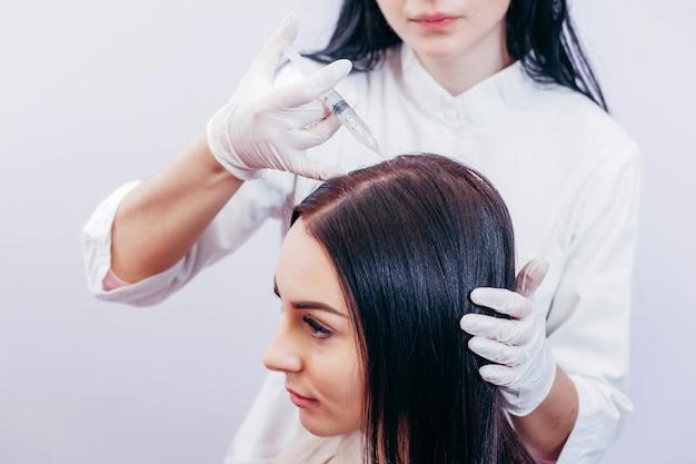 Молодая женщина с проблемой выпадения волос, получающей инъекции, крупным планом