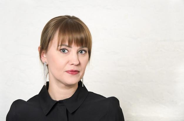 머리를 가진 젊은 여자가 뒤로 당겨서 흰 벽에 둥근 고리가있는 검은 드레스 앞머리