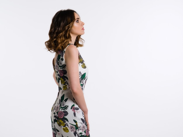 Young woman with haircut in dress looking in profile