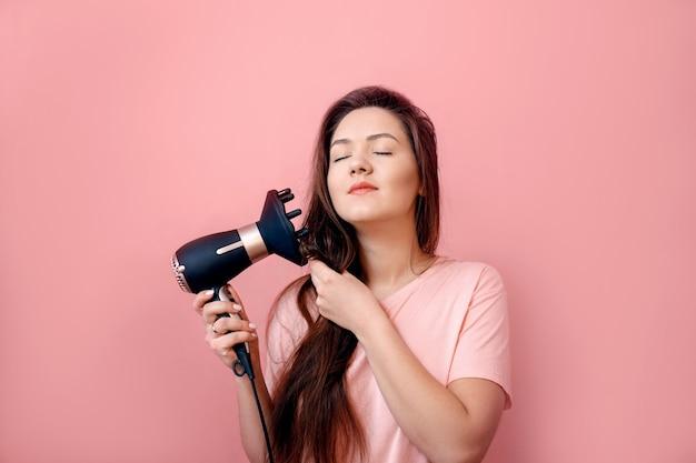 Молодая женщина с феном в руках на розовом фоне