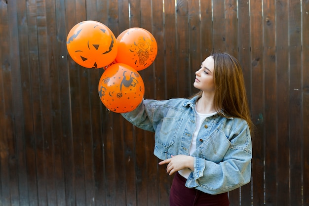 Young woman with halloween inflatable orange ballons on brown background