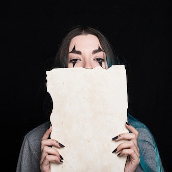 Young woman with halloween makeup holding piece of paper