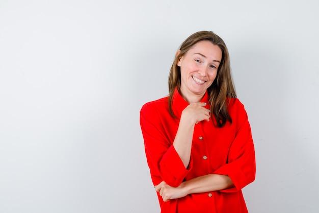 Giovane donna con la mano sul petto in camicetta rossa e guardando felice, vista frontale.