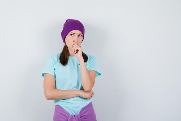 Giovane donna con la mano sulla bocca, che pensa a qualcosa in maglietta blu, berretto viola e sembra pensierosa. vista frontale.