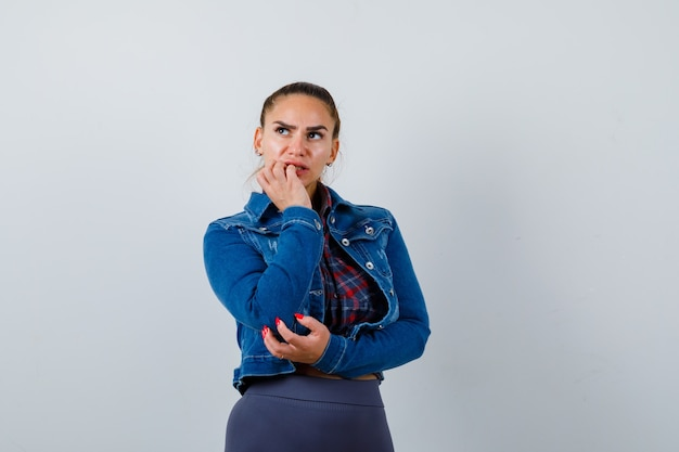 市松模様のシャツ、ジーンズのジャケットと思慮深く、正面図で顎に手を持っている若い女性。