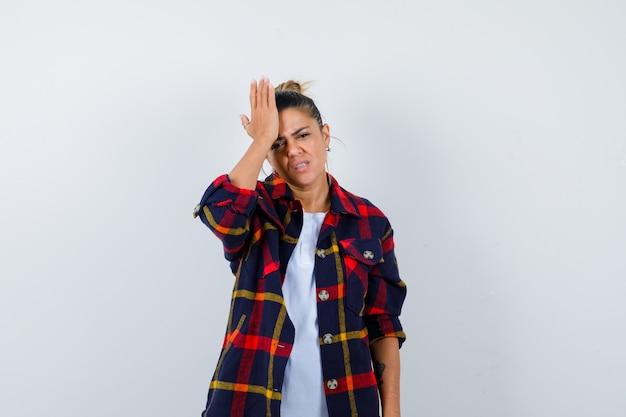 市松模様のシャツを着て頭に手を持って失望している若い女性、正面図。