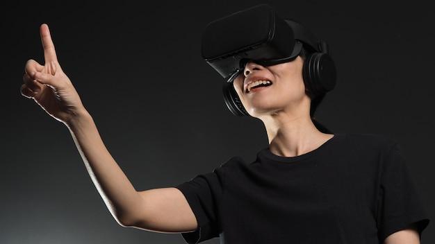 Молодая женщина с поднятой рукой в очках vr-гарнитуры