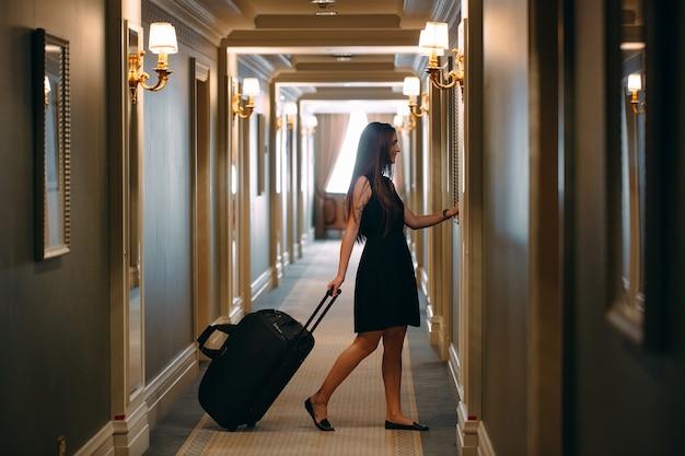 Молодая женщина с сумочкой и чемоданом в элегантном костюме идет по коридору отеля в свою комнату.