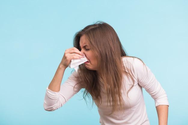 ハンカチを持つ若い女性。孤立した病気の少女は青い壁に鼻水があります