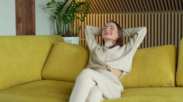 自宅で居心地の良い黄色のソファでリラックスし、後ろに寄りかかって、リビングルームの快適なソファでストレッチしている頭の後ろに手を持っている若い女性