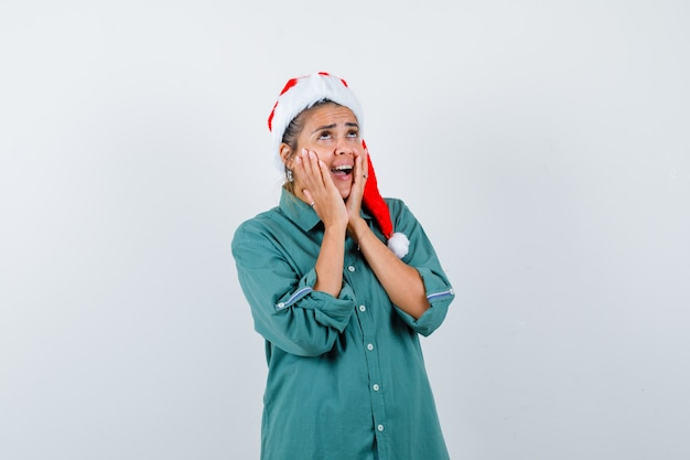 Giovane donna con le mani sulle guance, aprendo la bocca in camicia, cappello da babbo natale e guardando inorridita. vista frontale.