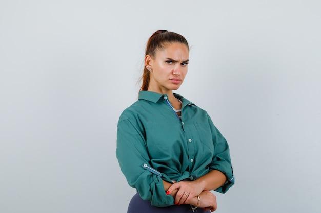 緑のシャツを着て、彼女の前に手を持って、意地悪に見える若い女性。正面図。