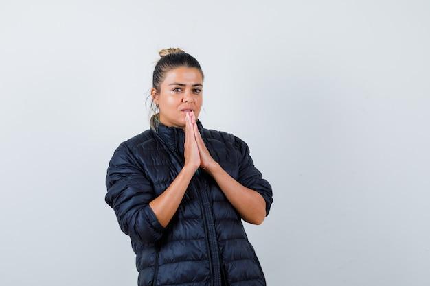 복어 재킷을 입고 기도하는 몸짓을 하고 희망찬 앞모습을 바라보는 손을 가진 젊은 여성.
