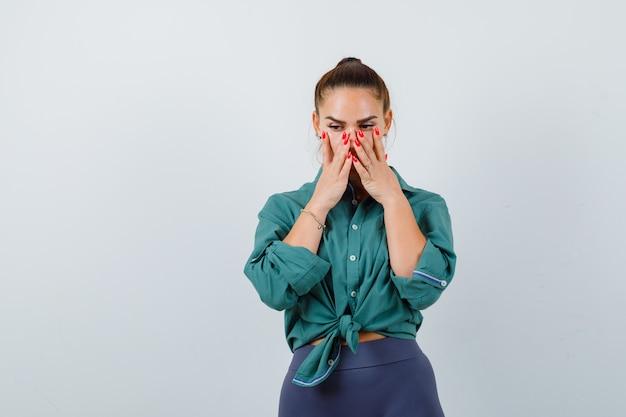 Молодая женщина с руками на лице в зеленой рубашке и тревожно глядя, вид спереди.