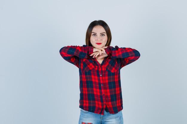 あごの下に手を持ち、チェックのシャツ、ジーンズ、魅力的に見える手にあごをもたれている若い女性。正面図。