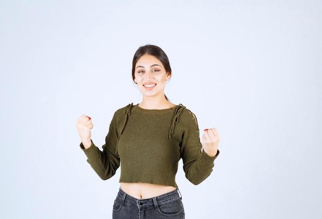 彼女の手のひらを示す幸せな表情を持つ若い女性