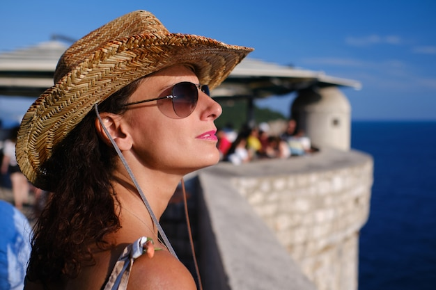 Young woman with hat at the city walls, old town, dubrovnik. croatia. .