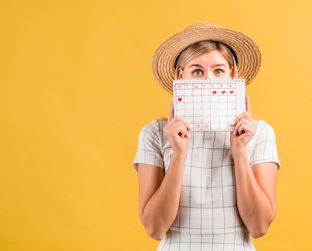 Young woman with hat covering her face with menstruation calendar