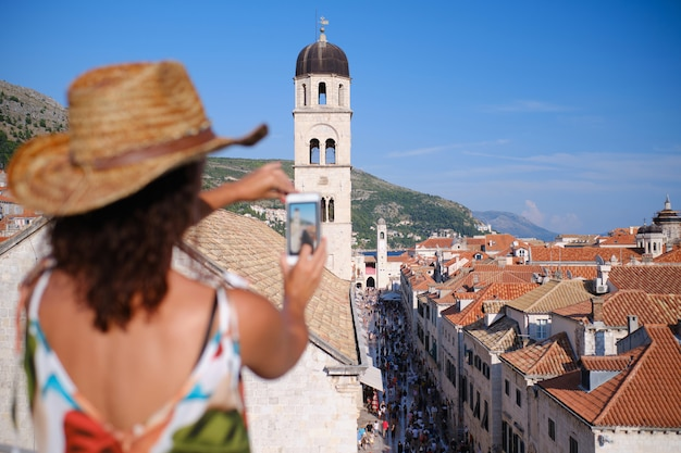 Young woman with hat takes photo with mobile in dubrovnik, croatia