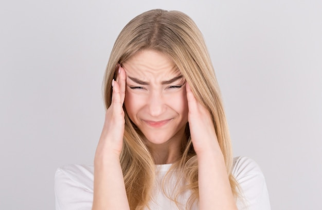 Young woman with a headache holds her temples with her hands. health, migraine and headache concept.