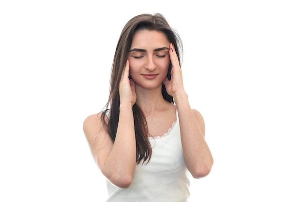 Молодая женщина с головной болью, изолированной на белой стене