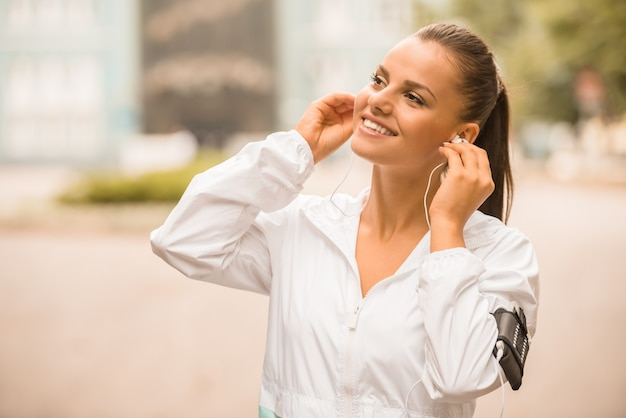 Young woman with headphone during morning exercises.