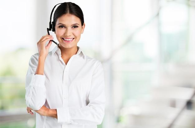 ヘッドフォン、コールセンター、またはサポートの概念を持つ若い女性