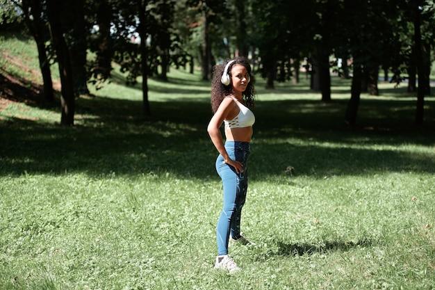 헤드폰을 끼고 공원에서 체조를 하는 젊은 여성