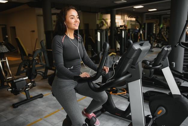 ジムやフィットネスセンターでエアロバイクの練習をしているヘッドフォンを持つ若い女性。ジムの若いスポーティな女性はスマートフォンから音楽を聴きます。有酸素運動をしている女性。