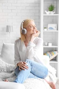 Молодая женщина с наушниками, наслаждаясь любимой музыкой и сидя на диване