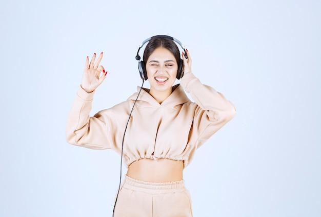 音楽とウィンクルを楽しんでいるヘッドフォンを持つ若い女性