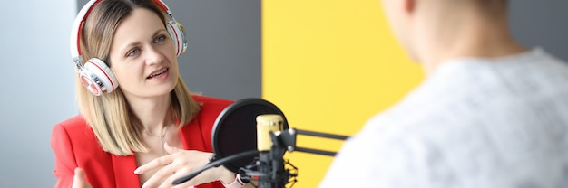 Young woman with headphones interviewing man on radio work in journalism concept