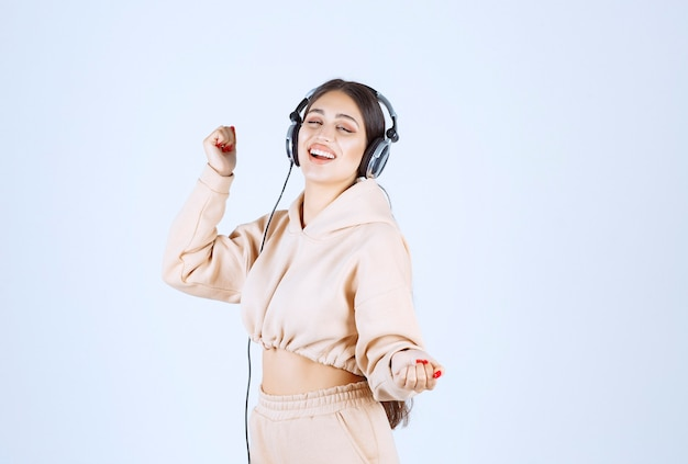 Young woman with headphones listening to the music and dancing