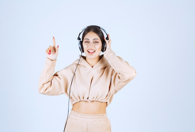 Giovane donna con le cuffie che ascolta la musica e balli