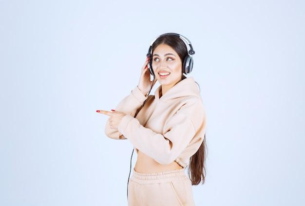 Giovane donna con le cuffie che indicano o che notano qualcuno a sinistra