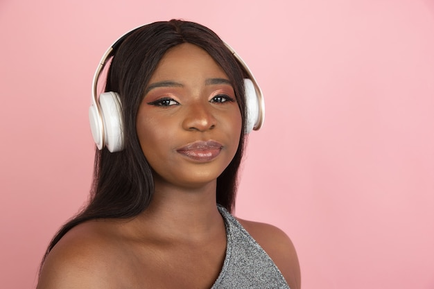 Young woman with headphones portrait on pink studio wall