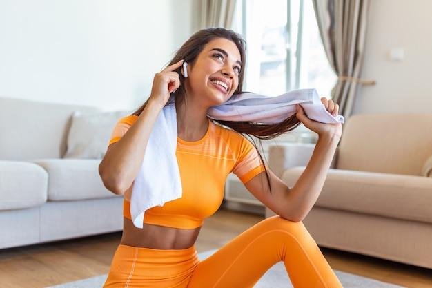 운동 후 휴식하는 헤드폰으로 젊은 여자.