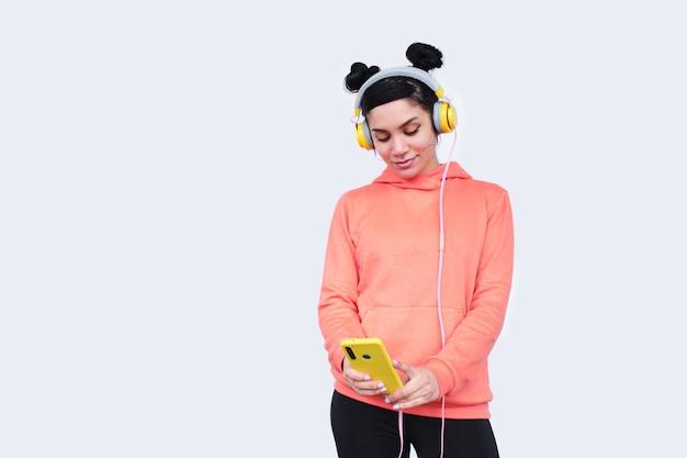 흰 벽에 휴대 전화를 사용 하여 헤드폰을 가진 젊은 여자