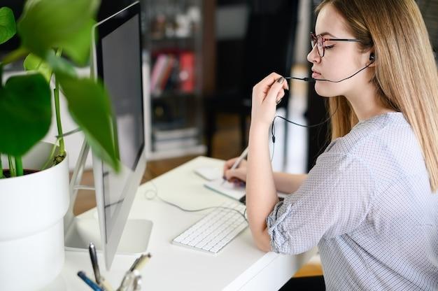 ヘッドフォンで作業、学習、コンピューターで話している若い女性。高品質の写真