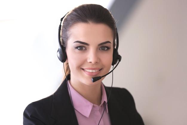 Молодая женщина с гарнитурой, работающая в офисе
