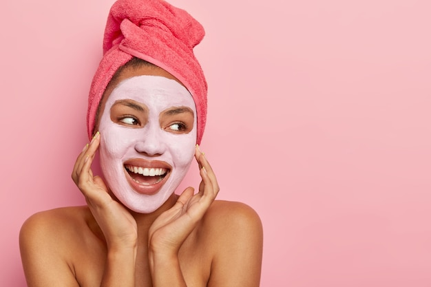 Young woman with healthy fresh dark skin applies nourishing clay mask, stands with bare shoulders, looks happily away, has wrapped towel on head, takes bath, looks aside with cheerful expression