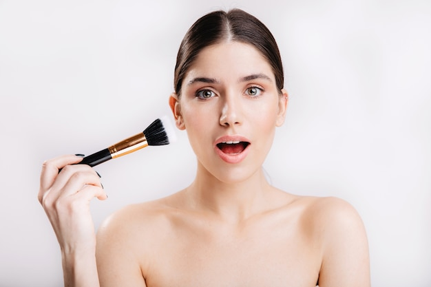 Young woman with healthy skin posing in surprise with brush for foundation on white wall.