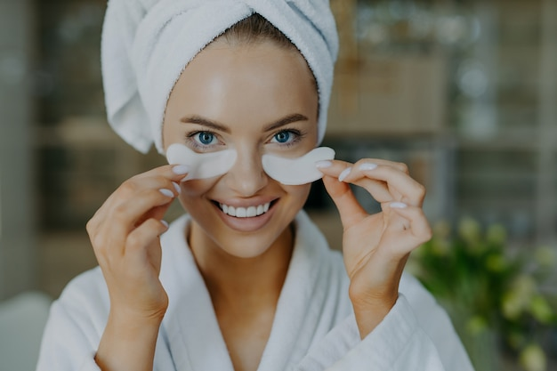 Young woman with healthy skin takes off beauty patches from under eyes